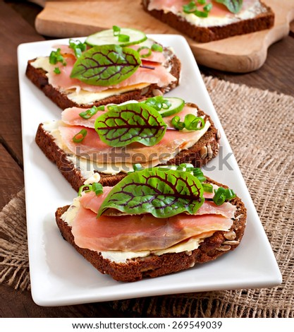 Small snacks sandwiches with salty salmon fish - stock photo