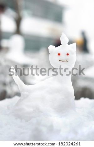 Small snow sculpture in the shape of a cat - stock photo