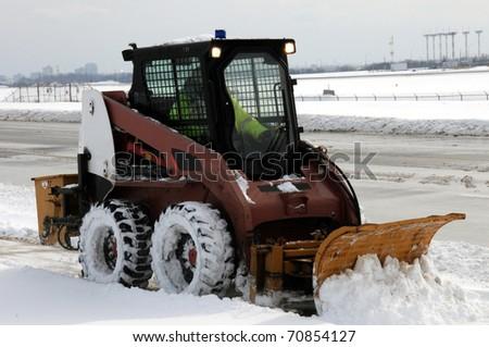 Small snowplow plowing sidewalk after heavy snowfall - stock photo