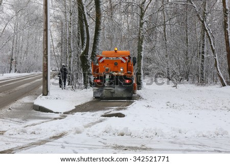 Small snowplow removing snow from sidewalk