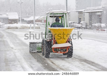 Small snowplow removing snow from sidewalk and sprinkled salt antifreeze - stock photo