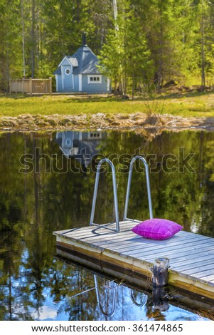 Small soft pillow lies on a wooden jetty next to a Finnish sauna, and a beautiful lake and forest in the background.Picturesque natural landscape.The land of lakes.Finland.Europe. - stock photo