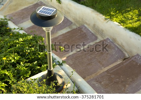 small solar garden light in a flower bed with stones