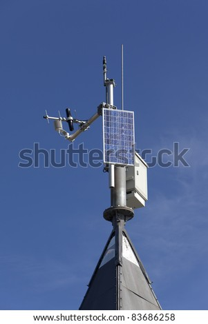 Small solar powered hitech meteo station over blue sky and clouds - stock photo