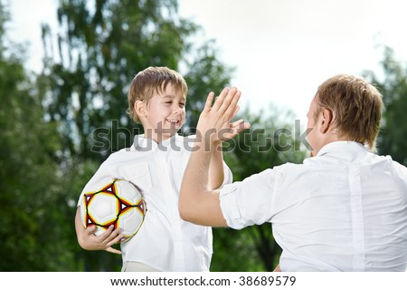 Small son - the football player welcomes the father, summer - stock photo