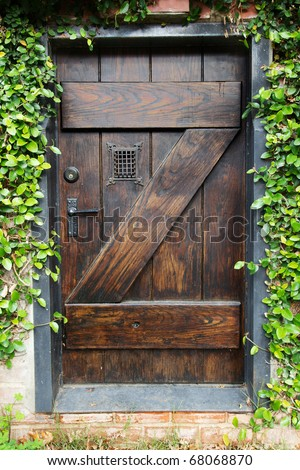 Small Spanish style dark stained wood door to secret garden with grated window - stock photo