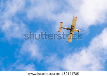 Small sport plane from below with blue sky - stock photo