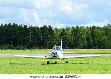 Small sports airplane parking on grass - front view - stock photo