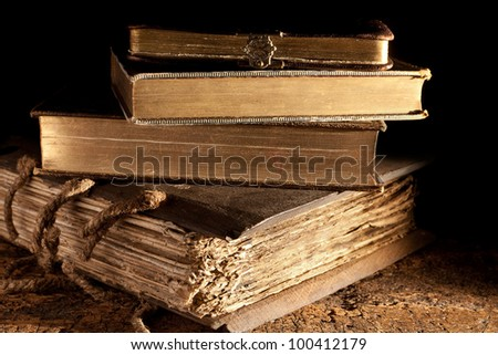 Small stack of antique books in weathered grungy state and gold edged - stock photo