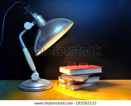 Small stack of books with glasses and vintage lamp in front of black wall - stock photo