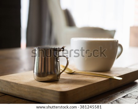 Small stainless steel syrup jug for coffee latte, background concept - stock photo