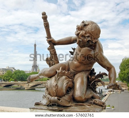 Small statue of a cherub on the Pont Alexandre III with eiffel tower in background in Paris. - stock photo