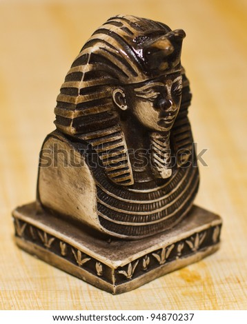 Small statue of egyptian pharaoh Tutankhamun, side view, over a papyrus paper background, selective depth of field. - stock photo