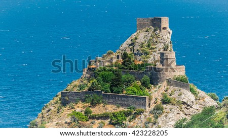 Small stone built building on the top of the mediterranean mount with the amazing azure blue sea waters in the background, Sicily, Italy - stock photo