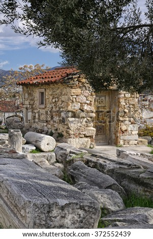 Small stone hut near the Theater of Dionysus Eleuthereus in area of the Acropolis of Athens. In the foreground could see the remains of ancient marble columns.