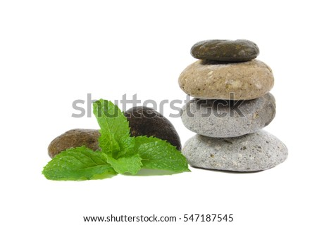 Small stones and peppermint leaves for warm spa therapy isolated on a white background