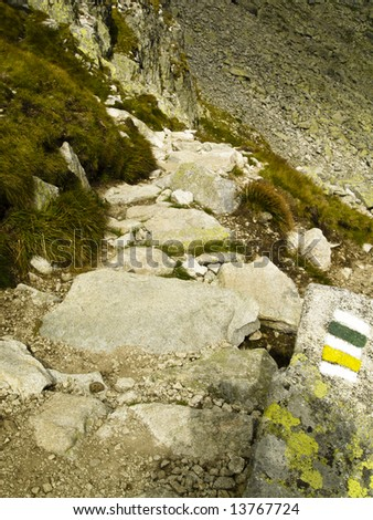 Small stones green and yellow trail in Tatra mountain - stock photo