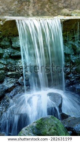 small stream flows on stones photographed close up - stock photo