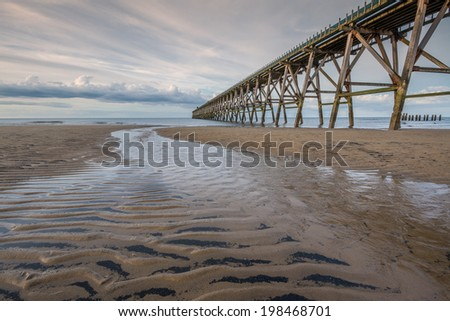 Small Stream on a Sandy Beach with an Old Pier - stock photo
