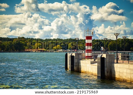 small striped lighthouse at the pier in the port of Klaipeda, Lithuania - stock photo