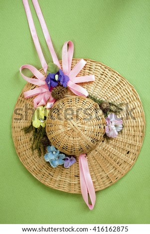 Small summer straw hat for doll isolated over green background - stock photo