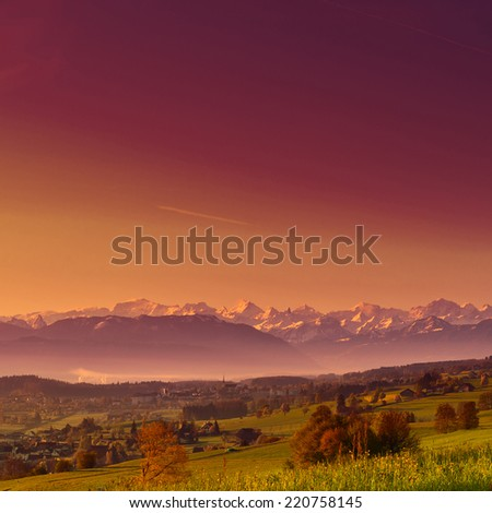 Small Swiss Town Surrounded by Meadows on the Background of Snow-capped Alps, Sunrise, Instagram Effect - stock photo