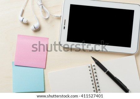Small tablet pc with blank area on touchscreen, in ear headset, notebook, sticky paper, and pen on wood table - stock photo