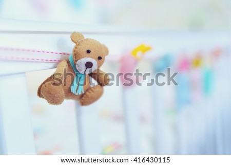 Small teddy bear hanging on baby bed - stock photo