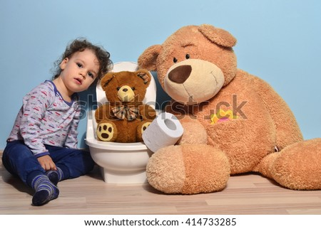 Small teddy bear sitting on the potty and playing with toilet paper. Cute kid potty training for pee and poo - stock photo