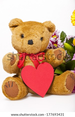 Small teddy bear with a red heart isolated in front of white Background