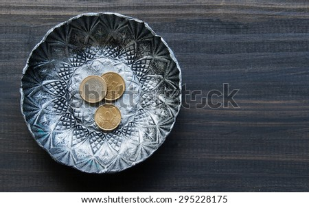small textured metal plate with euro coins on a wooden black background - stock photo