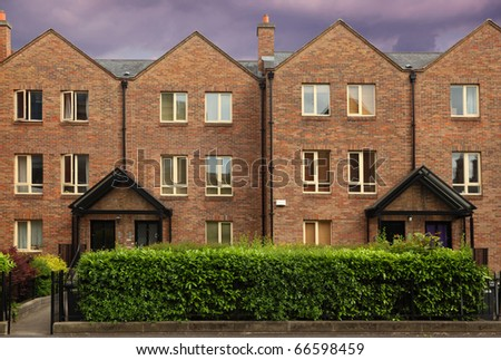 small three-story house stands beside road. windows, high green bushes, wrought-iron lattice - stock photo