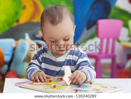 Small toddler or a baby child playing with puzzle shapes on a low table in a colorful children room in a nursery or preschool. - stock photo