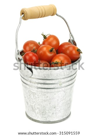 Small tomatoes on a small metal bucket on a white background      - stock photo