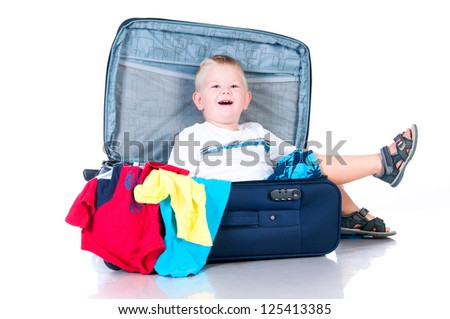 Small tourist collects things in a suitcase for travel - stock photo