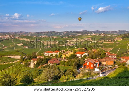 Small town among green hills and vineyards in Piedmont, Northern Italy. - stock photo