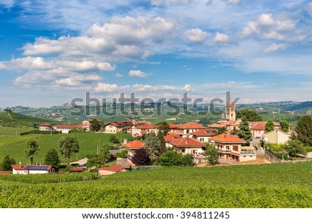 Small town among green vineyards under beautiful sky in Piedmont, Northern Italy.