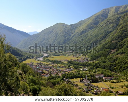 small town in the Maggia valley framed by high green, wooded mountains in Ticino, Switzerland