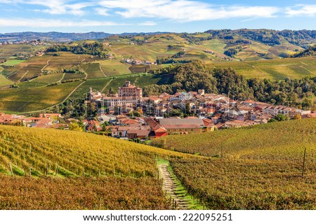 Small town of barolo among hills and autumnal vineyards in Piedmont, Northern Italy. - stock photo