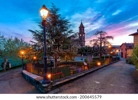 Small town square with illuminated lampposts and parish church on background under beautiful morning sky in Piedmont, Northern Italy. - stock photo