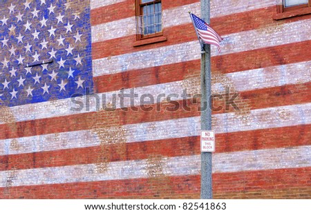 Small-town street scene in Illinois: American flag flapping in breeze by huge painted American flag fading from brick wall - stock photo