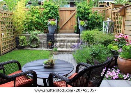 Small townhouse garden with patio furniture amidst blooming lavender. Small Townhouse Garden Patio Furniture Amidst Stock Photo