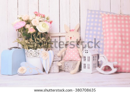 Small toy house, pony, toy bunny, pillows in  the children's room on wooden background - stock photo