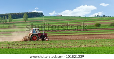 Small tractor harrow on the spring striped field - small scale agriculture