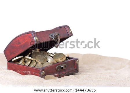 small treasure box open with gold coins inside part buried in the sand isolated on white background - stock photo