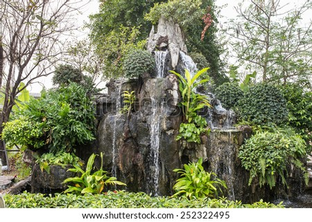 Small tropical garden waterfall - stock photo