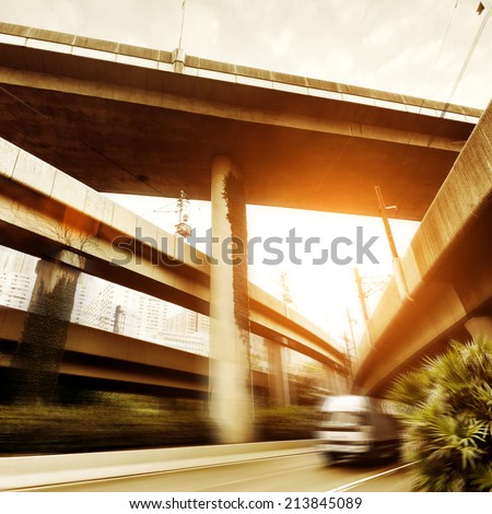 Small truck speeding under industrial bridges. Long exposure, burred motion. - stock photo