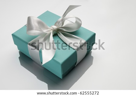 small turquoise box tied with a white ribbon - stock photo