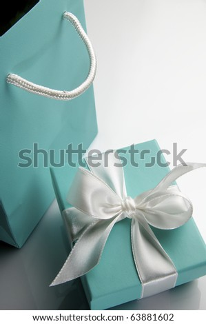 small turquoise box tied with a white ribbon and bag - stock photo