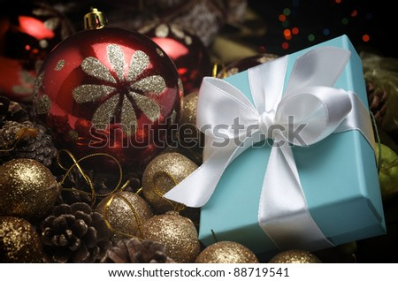 small turquoise box tied with a white ribbon and christmas decoration